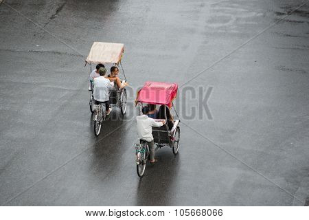 Cyclos drivers carry tourists in Hanoi, Vietnam.