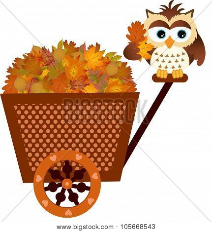 Owl on a cart with fall leaves