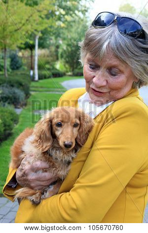 Senior woman holding a dachshund dog.