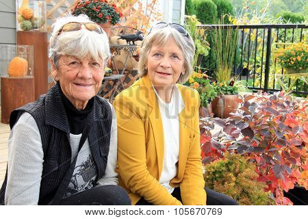 Two senior ladies,seated outside on a wood deck during autumn.