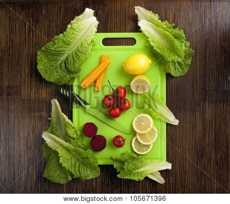 lemon , mini tomatoes carrot and beetroot an lettuce on green plastic cutting surface on wooden background