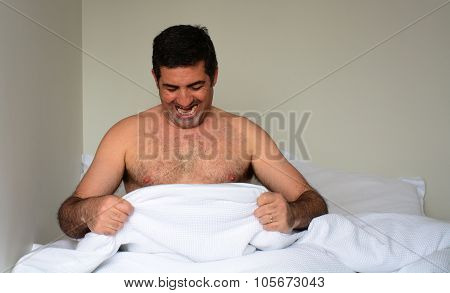 Happy Man In His Forties (40S) In Bed Looking Down At His Penis