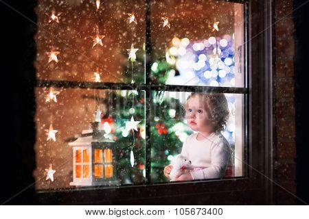 Little Girl Sitting At A Window On Christmas Eve