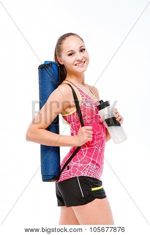 Portrait of a smiling fitness woman holding shaker and yoga mat isolated on a white background