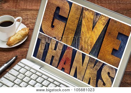Give thanks - Thanksgiving concept - text in vintage letterpress printing blocks on a laptop screen with a cup of coffee