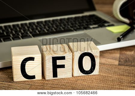 CFO (Chief Financial Officer) written on a wooden cube in front of a laptop