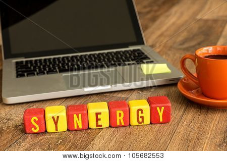 Synergy written on a wooden cube in front of a laptop