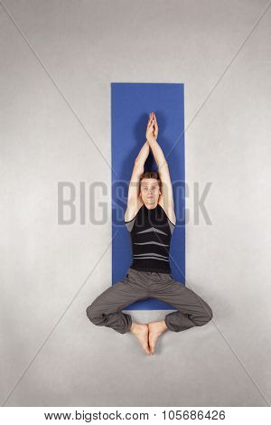 Overhead view of caucasian man practicing yoga on mat