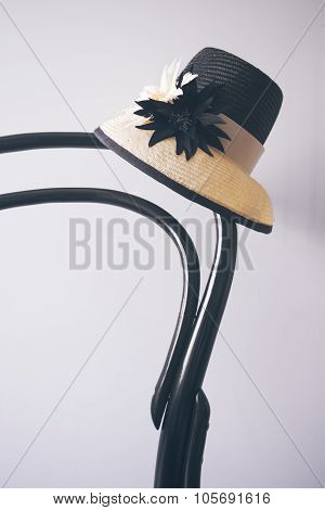 Ladies Dress Hat Sitting On A Vintage Black Wooden Chair