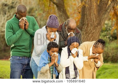 Sick family blowing their nose in parkland