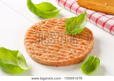 close up of raw burger patty with basil on white background