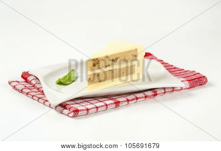 slice of unbaked nut cake on white square plate and checkered dishtowel