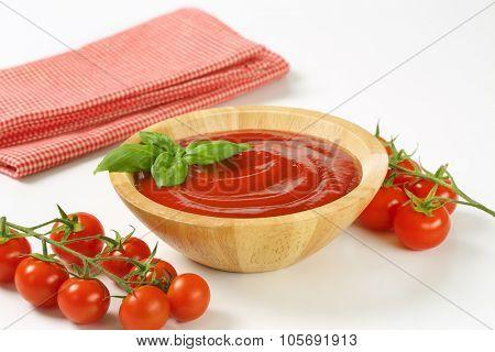 bowl of tomato puree, cherry tomatoes and checkered dishtowel on white background