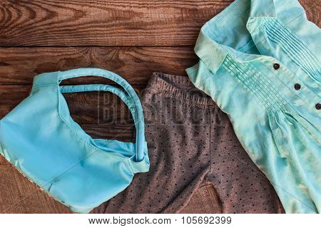 Teen clothing and accessories: shirt, leggings and handbag on wooden background