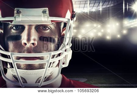 American football player looking at camera against american football arena