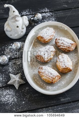 Cookies Madeleines With Powdered Sugar On The Oval Plate, Ceramic Santa Claus And Christmas Decorati