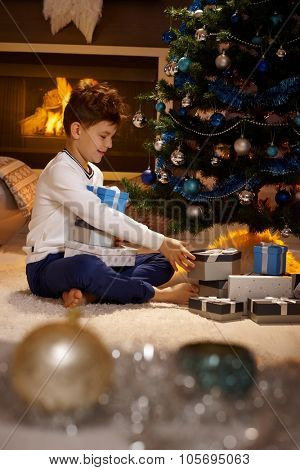 Excited little boy opening christmas presents, sitting on floor, by christmas tree.