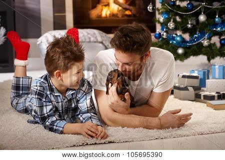 Happy little boy and father playing on floor with dachshund puppy at christmas time.