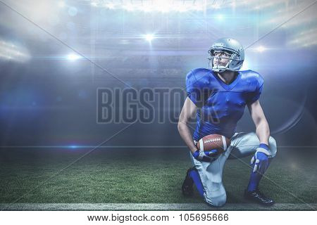 American football player with ball kneeling against american football arena