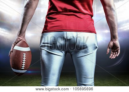 Mid section of sportsman with American football against sports pitch