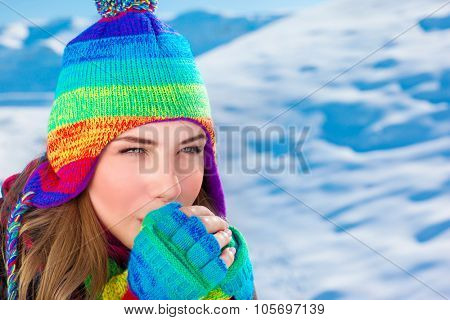 Portrait of young cute female wearing knitted colorful hat and gloves blowing warm air on her hands, winter holidays in the mountains covered with snow