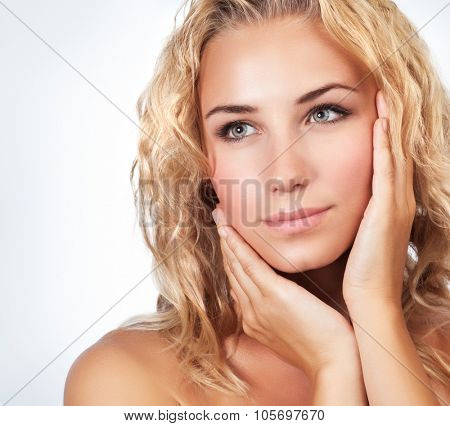 Portrait of beautiful gentle blond woman over clean background, using natural cosmetics in spa salon, beauty treatment