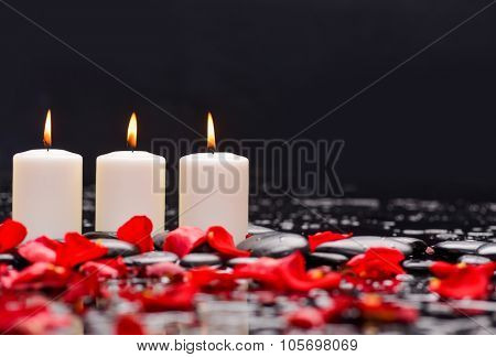 Red rose petals with three candle and therapy stones