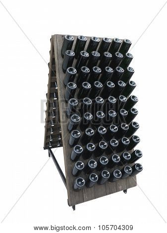Dark Bottles On A Wine Cellar Wooden Support Isolated Over White