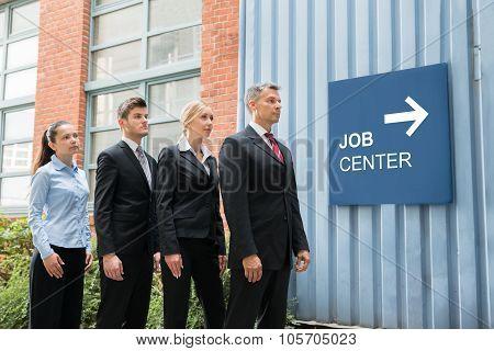 Businesspeople Standing Near The Job Center Signboard