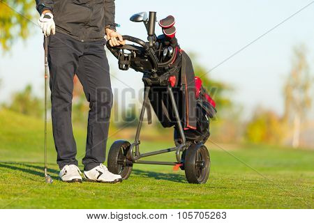 Man playing golf on green golf course holding trolley