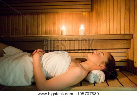 Pretty woman relaxing in the sauna in the spa