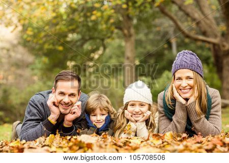Smiling young family with hands on cheeks on an autumns day