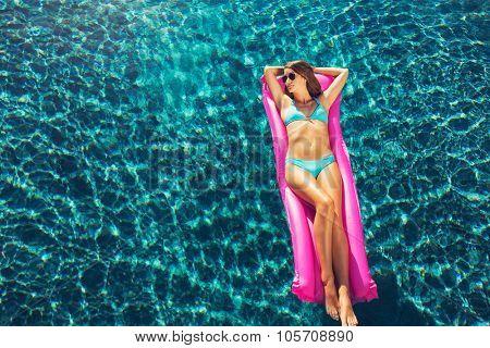 Beautiful sexy young woman in bikini relaxing floating on raft in luxury swimming pool