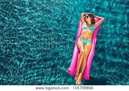 Beautiful sexy young woman in bikini relaxing floating on raft in luxury swimming pool
