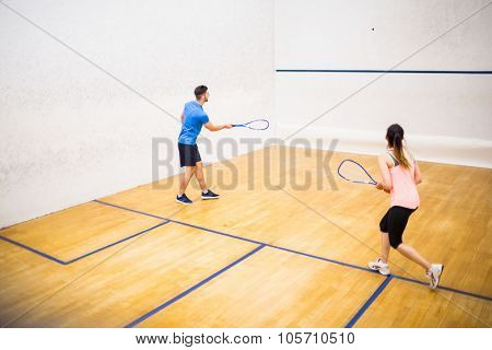 Couple playing a game of squash in the squash court