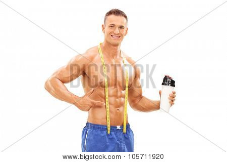 Young male athlete holding a bottle with protein shake and pointing towards it with his hand isolated on white background