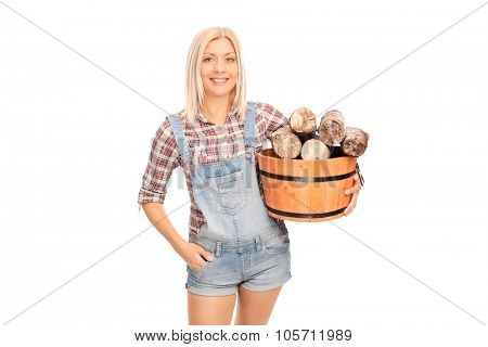 Young cheerful woman holding a bucket full of logs and looking at the camera isolated on white background