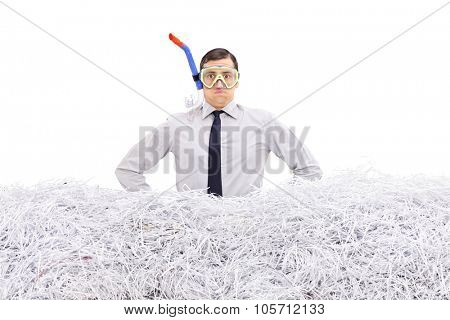 Young businessman with a diving mask standing in a pile of shredded paper isolated on white background