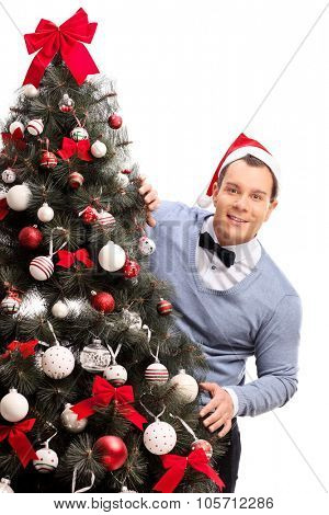 Vertical shot of a young man with Santa hat standing behind a Christmas tree isolated on white background