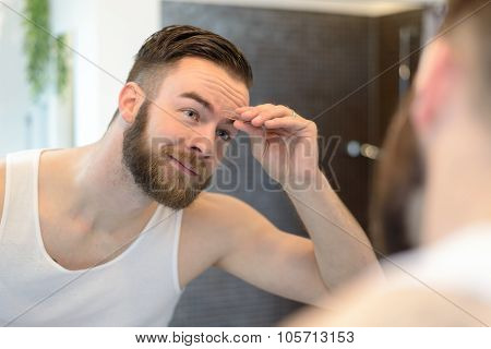 Young Man Using Tweezers