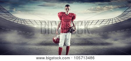 A serious american football player taking his helmet on her hand looking at camera against rugby stadium
