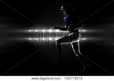 Silhouette American football player runing against spotlights