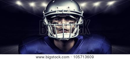 Portrait of determined American football player in uniform against rugby stadium
