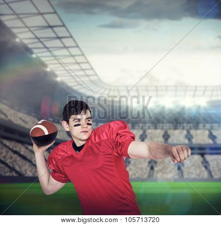 American football player throwing a ball against large football stadium with lights