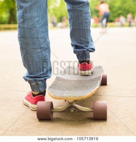 Teenage girl practicing riding long board.
