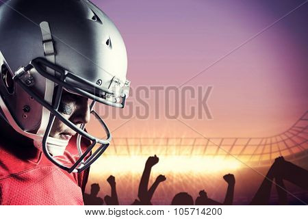 American footballer looking down against football stadium with cheering crowd