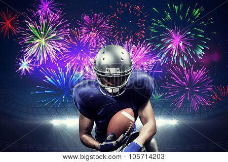 American football player holding ball while kneeling against fireworks exploding over football stadium