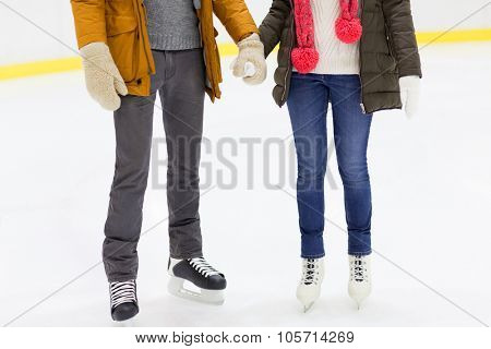 people, love, winter and leisure concept - close up of happy couple holding hands and skating on ice rink