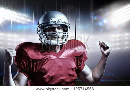 Portrait of American football player cheering with clenched fist against american football arena