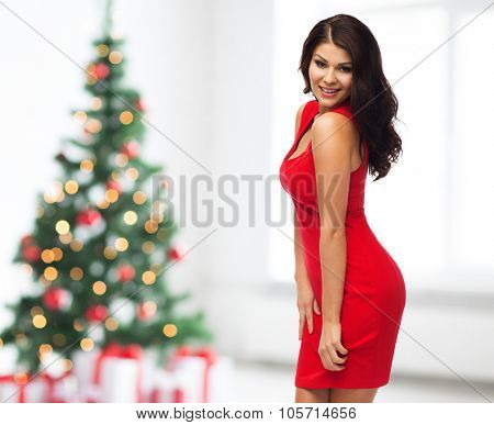 people, holidays and fashion concept - beautiful sexy woman in red dress over room with christmas tree and gifts background